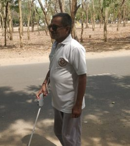 Gaganbhai walking with Saarthi attached to white cane