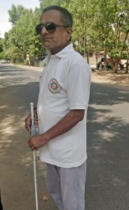 Gaganbhai standing with Saarthi attached to white cane