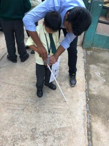 Torchit team member training their youngest beneficiary - a 5 year old kid about the use of Saarthi device at Meghalaya Blind School