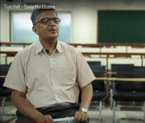 Dilipbhai sitting with Saarthi in his hands - he is a visually challenged man from Ahmedabad