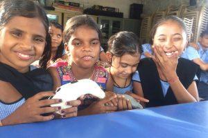 4 schools girls in uniform sitting with Saarthi in hand